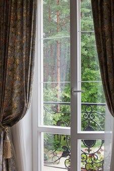 녹색 나무를 볼 수 있는 흰색 창