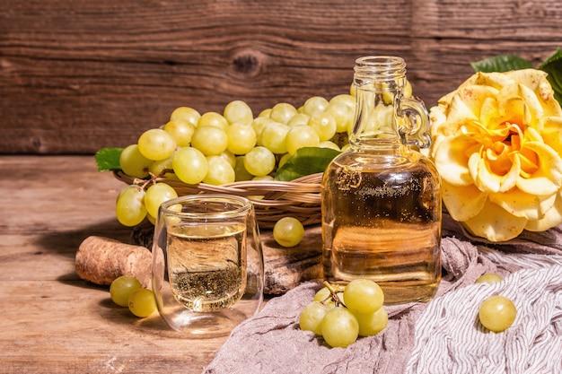 Белое вино и виноград в плетеной корзине. свежие фрукты, стакан и бутылка. современный жесткий свет, темная тень. старые деревянные доски фон, копия пространства