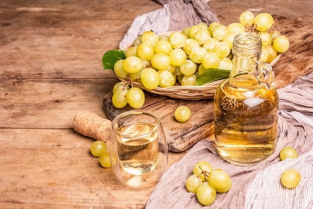 Белое вино и виноград в плетеной корзине. свежие фрукты, стакан и бутылка. старые деревянные доски фон, копия пространства