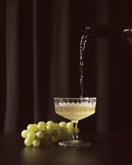어두운 배경에 화이트 와인과 포도
