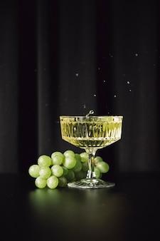 暗い背景に白ワインとブドウ