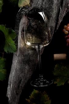 화이트 와인과 포도. 나무 테이블에 코르크가 있는 빈티지한 분위기의 와인과 포도. 평면도.