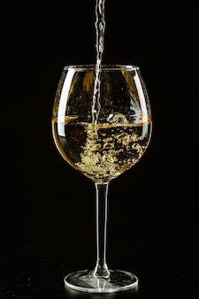 White wine being poured in a wine glass on a dark background