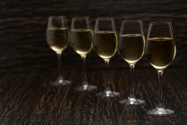 White wine on a black wooden table, close up.