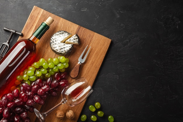 White wine bottle, bunch of grapes, cheese and wineglass on wooden board