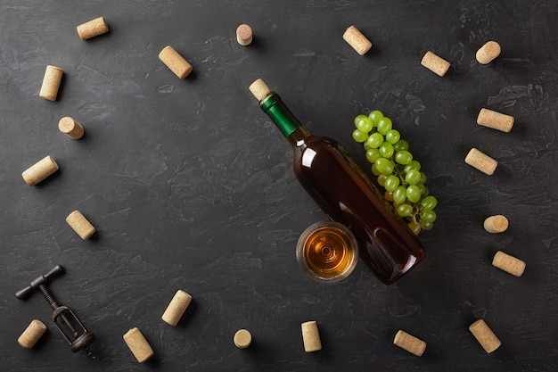White wine bottle, bunch of grapes and wineglass with corks and corkscrew on black background. top view with copy space.