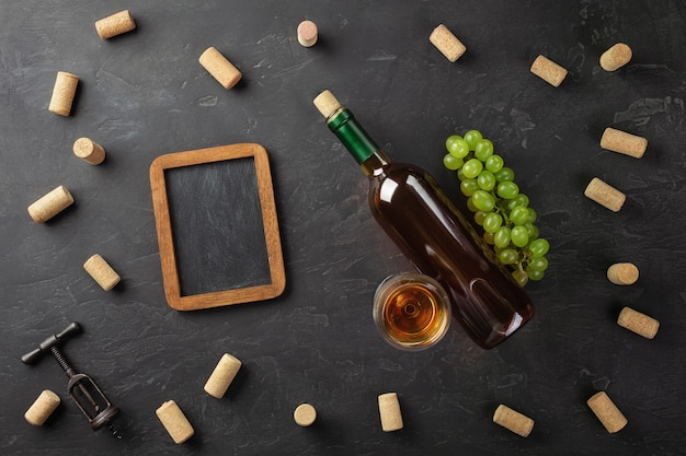 White wine bottle, bunch of grapes, wineglass with corks, corkscrew and chalk board on black background. top view with copy space.