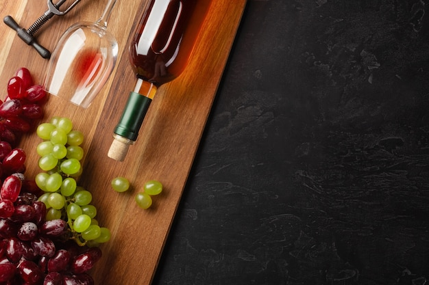 White wine bottle, bunch of grapes and wineglass on wooden board and black background. top view with copy space.
