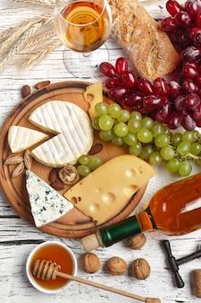 Бутылка белого вина, виноград, мед, сыр и рюмка на белой деревянной доске. вид сверху с копией пространства.