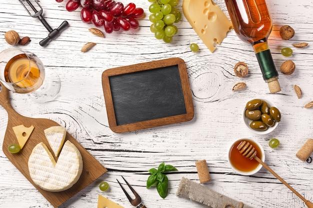 白い木の板に白ワインのボトル、ブドウ、蜂蜜、チーズ、ワイングラス、チョークボード。コピースペースのある上面図。