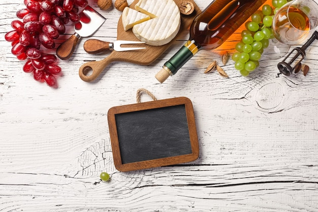 White wine bottle, grape, honey, cheese, wineglass and chalk board on white wooden board. top view with copy space.