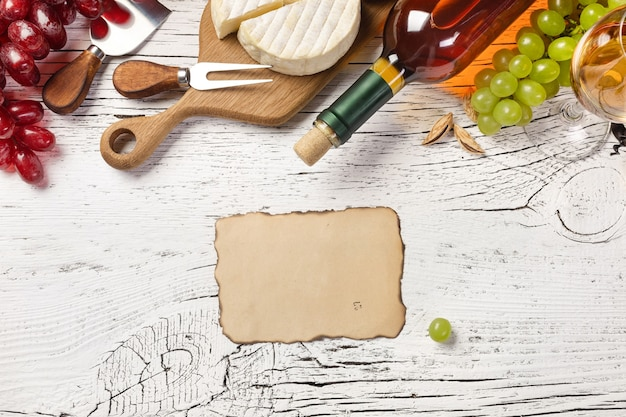 White wine bottle, grape, honey, cheese, wineglass and sheet of old paper on white wooden board. top view with copy space.
