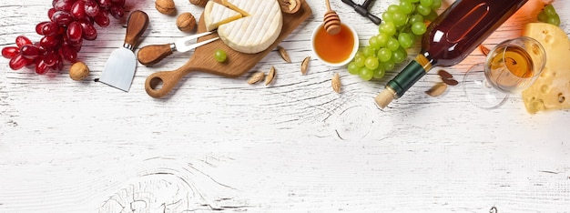 White wine bottle, grape, honey, cheese and wineglass on white wooden board. panoramic top view with copy space for your text.