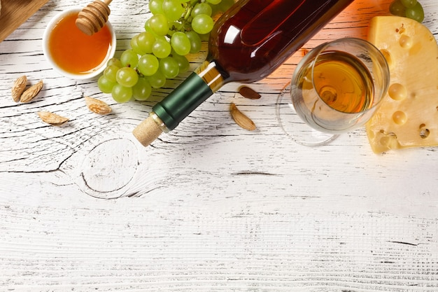 White wine bottle, grape, honey, cheese and wineglass on white wooden board. top view with copy space.