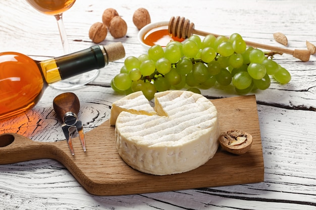 White wine bottle, grape, honey, cheese and wineglass on white wooden board