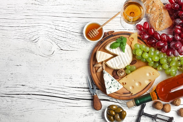 White wine bottle, grape, honey, cheese and wineglass on white wooden board.