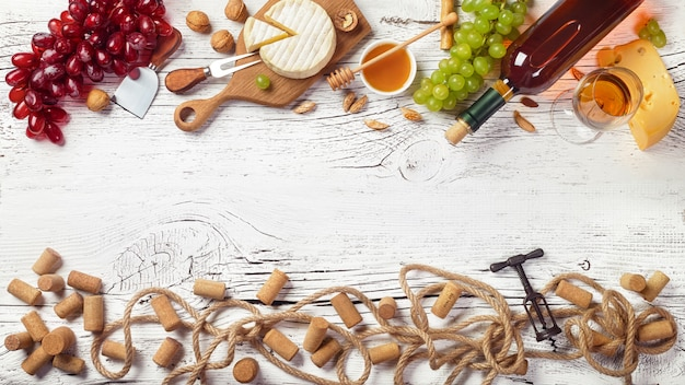 White wine bottle, grape, honey, cheese, wineglass with corkscrew, corks and rope on white wooden board