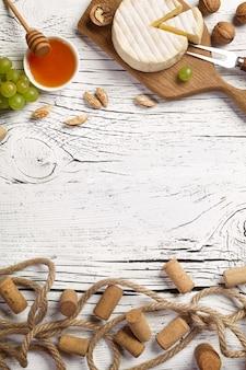 白ワインのボトル、ブドウ、蜂蜜、ナッツ、チーズを白い木の板に。コピースペースのある上面図。