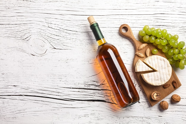 White wine bottle, grape, honey, nuts and cheese on white wooden board. top view with copy space.