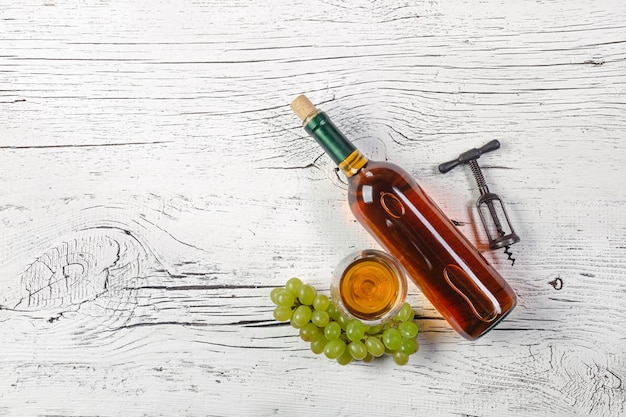White wine bottle, grape and wineglass on white wooden background