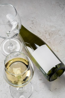 White wine bottle with empty label and glasses, mockup logo on white background