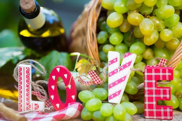 화이트 와인 병, 어린 포도나무, 그리고 녹색 봄 배경에 대한 포도 다발