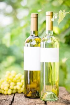 緑の春を背景に古い木製のテーブルの上の白ワインのボトルとブドウの房