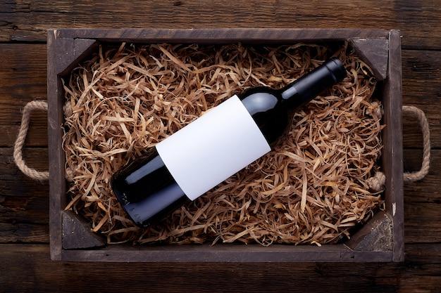 開いた木製の箱に詰められた白ワインのボトル