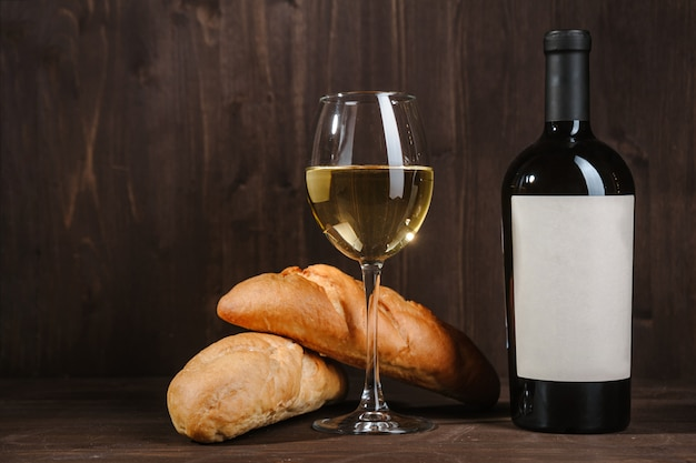 White wine composition with bread bottle and wineglass on wooden room