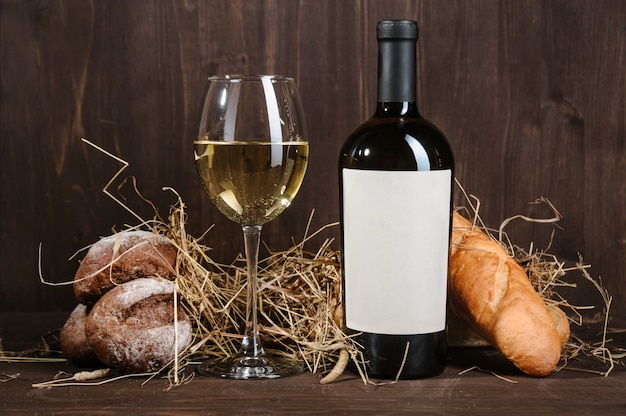 White wine composition with bread bottle and wineglass on wooden table