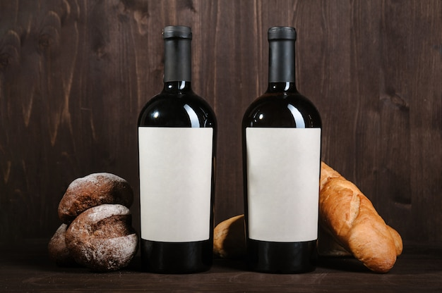 White wine composition with bread, two bottles and wineglass on wooden room