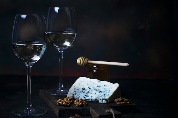 White wine in fine glass with blue cheese, honey, walnuts on dark