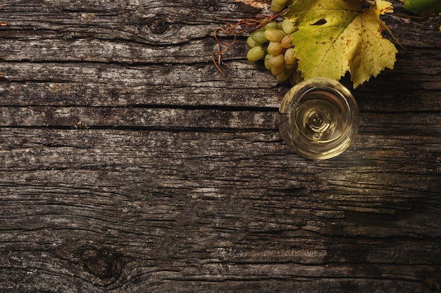 White wine in a glass, grapes and grape branches on the table. top view. copy space for you text.