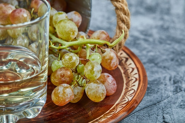 Vino bianco in un bicchiere con un grappolo d'uva verde intorno.