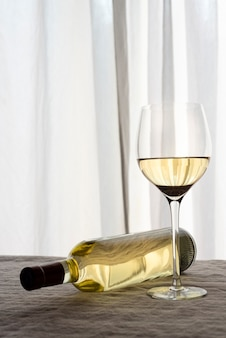 White wine glass with fallen bottle on table