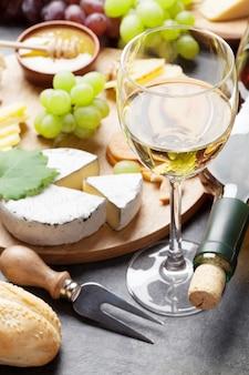 돌 테이블에 화이트 와인, 포도, 빵, 치즈 접시, 꿀