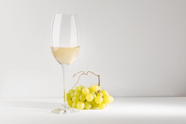 ガラスのゴブレットの白ワインと白いテーブルの上のブドウの束。明るい背景。