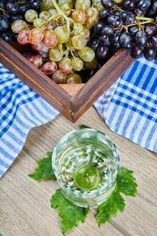 Белое вино в бокале с гроздью зеленого винограда вокруг.