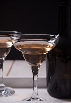 Белое вино в бокалах, бутылка на белом деревянном подносе. ужин на двоих.