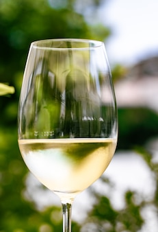 Белое вино в роскошном ресторане на террасе летнего сада. дегустация вин на винодельне в ...