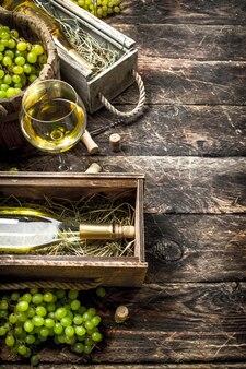녹색 포도와 오래 된 상자에 화이트 와인입니다. 나무 테이블에.