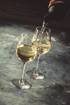 White wine pouring into glasses, close up