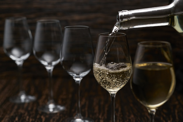 White wine pouring into glasses from bottle