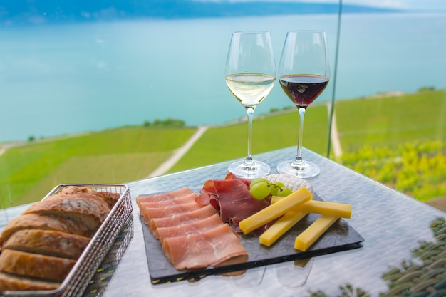 White wine and red wine with mix snack , cheese ,smoked ham salami platter and bread at vineyard