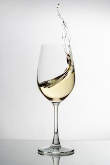 Белое вино брызгает из элегантной рюмки