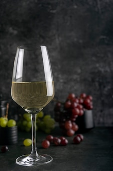 White wine in a wine glass with red and green grapes in the dark marble background