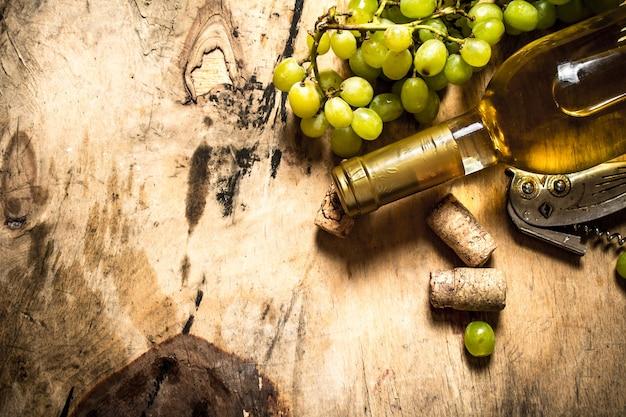 ブドウの房と白ワイン。木製の背景に。
