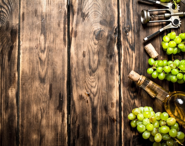 木製のテーブルにコルク栓抜きとブドウの枝を持つ白ワイン