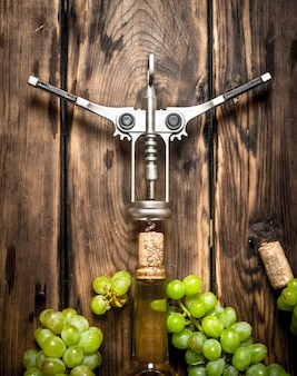 코르크 마개와 포도 가지가있는 화이트 와인. 나무 테이블에.