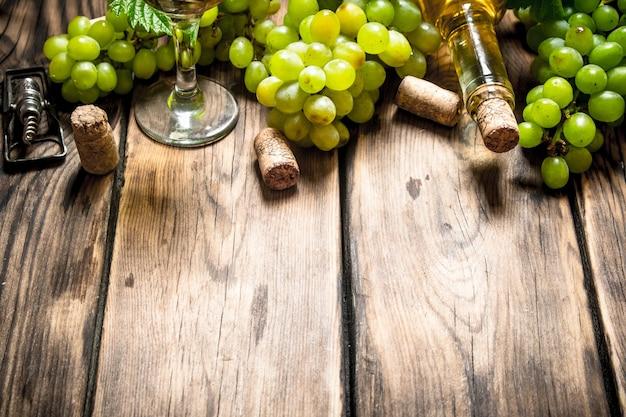 木製のテーブルに白ブドウの枝を持つ白ワイン。